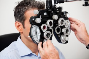 Optometrist adjusting panels of phoropter while examining his patient